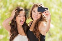 2 привлекательных девушки смешанных гонки делая Selfies с Smartphone Стоковые Изображения