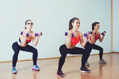 3 привлекательных девушки спорта делая сидеть на корточках с гантелями в классе фитнеса Стоковые Фото