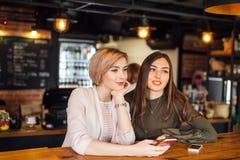 2 привлекательных друз маленькой девочки беседуя на smartphone на кафе Стоковые Фото