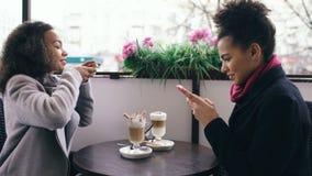 2 привлекательных друз смешанных гонки женских фотографируя кофейные чашки совместно используя камеру smartphone пока сидящ внутр Стоковое Изображение