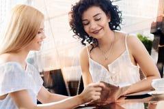 2 привлекательных женских друз смотря тетрадь Стоковые Фото