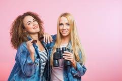 2 привлекательных женщины в куртках джинсов с солнечными очками и биноклями Стоковое фото RF