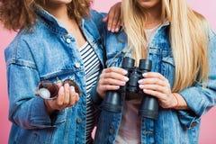 2 привлекательных женщины в куртках джинсов с солнечными очками и биноклями Стоковая Фотография RF