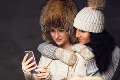 2 привлекательных женщины используя smartphone Стоковая Фотография