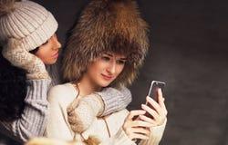 2 привлекательных женщины используя smartphone Стоковое Изображение