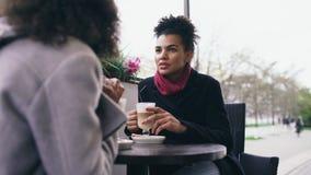 2 привлекательных женщины смешанных гонки говоря и выпивая кофе в кафе улицы Друзья имеют потеху после посещая продажи мола Стоковое Фото