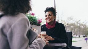 2 привлекательных женщины смешанных гонки говоря и выпивая кофе в кафе улицы Друзья имеют потеху после посещая продажи мола Стоковые Изображения RF