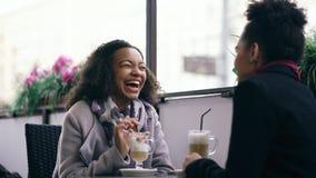 2 привлекательных женщины смешанных гонки говоря и выпивая кофе в кафе улицы Друзья имеют потеху после посещая продажи мола Стоковые Фотографии RF