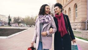 2 привлекательных женщины смешанных гонки с хозяйственными сумками говоря и идя вниз с улицы Подруги имеют потеху позже Стоковые Фотографии RF