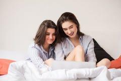 2 привлекательных женщины с ноутбуком в кровати стоковое фото rf