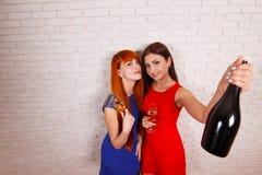 2 привлекательных жизнерадостных девушки имея потеху и выпивая шампанское Стоковая Фотография