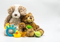 2 привлекательных заполненных плюшевого медвежонка полагаясь на одине другого окруженном младенцем забавляются Стоковое Изображение