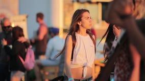 2 привлекательных кавказских девушки активно танцуют в под открытым небом толпить партии пляжа сток-видео