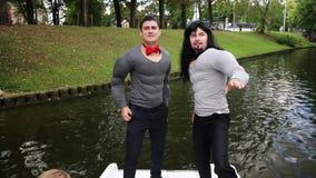 2 привлекательных люд нося поддельную мышцу проложили костюмы танцуют и поют в шлюпке видеоматериал