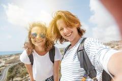 2 привлекательных маленькой девочки путешествуют совместно, делают selfie на pho Стоковое фото RF