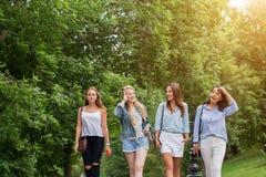 4 привлекательных молодой женщины говоря идти совместно стоковые фотографии rf