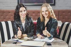 2 привлекательных молодой женщины показывая большой палец руки вверх говорить встречи компьтер-книжки стола cmputer бизнесмена де стоковая фотография