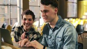 2 привлекательных молодые люди, парень и девушка в их 20 ` s, тратящ время совместно, смеющся над и ищущ сетью акции видеоматериалы