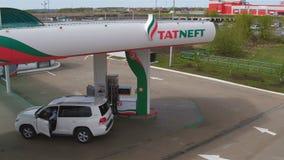 Приводы автомобиля к бензину Tatneft против взгляда верхушки зданий акции видеоматериалы