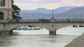 Привод автомобиля за небольшим каменным мостом над рекой в европейском городе видеоматериал