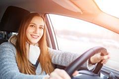 Привод молодой женщины автомобиль в зиме стоковое изображение rf