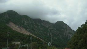 Привод POV через красивую природу с зелеными деревьями и крутыми наклонами горы, curvy дорогой асфальта, пасмурным днем акции видеоматериалы