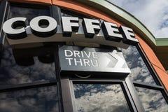 Привод кофе через знак с отражает от стеклянного окна Стоковое Фото