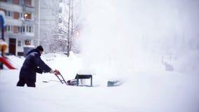 Привратник освобождает след с снегоочистителем в дворе жилого дома видеоматериал