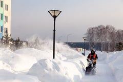 Привратник России Kemerovo 2019-02-22 в равномерном оранжевом жилете очищает мостовую, пешеходную дорожку от снега с машиной снег стоковые изображения rf