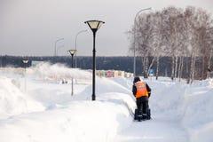 Привратник России Kemerovo 2019-02-22 в равномерном оранжевом жилете очищает мостовую, пешеходную дорожку от снега с машиной снег стоковые изображения