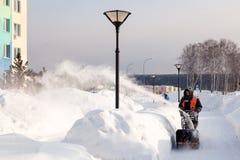 Привратник России Kemerovo 2019-02-22 в равномерном оранжевом жилете очищает мостовую, пешеходную дорожку от снега с машиной снег стоковые фото