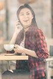 Привлекательная азиатская девушка используя smartphone и выпивающ кофе в кафе Стоковые Изображения RF