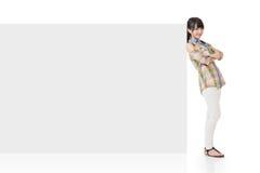 Привлекательная азиатская женщина полагается на пустой доске стоковое изображение