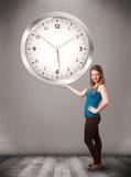 Привлекательная дама держа огромные часы Стоковое фото RF
