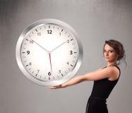 Привлекательная дама держа огромные часы Стоковые Изображения RF