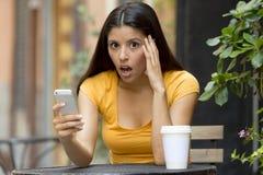Привлекательная латинская женщина сотрясенная на ее умном телефоне стоковые изображения rf