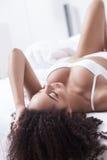 Привлекательная африканская девушка расслабляющая в спальне Стоковые Изображения