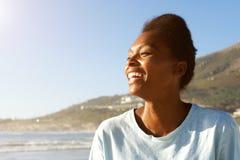 Привлекательная африканская женщина стоя outdoors и смеясь над Стоковое Изображение