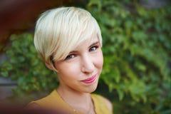 Привлекательная белая женщина принимая selfie против фона загородки плюща Стоковые Фото
