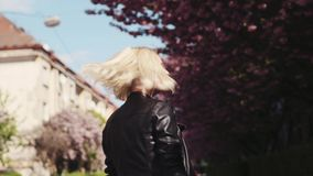 Привлекательная белокурая девушка в кожаной куртке наслаждаясь вишневым цветом в городе, поворотами к камере и улыбками прелестно видеоматериал