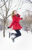 Привлекательная белокурая девушка с перчатками, красное пальто и красная шляпа представляя в зиме идут снег. Красивая женщина в пе Стоковая Фотография