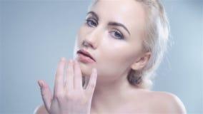 Привлекательная белокурая женщина представляя на белой предпосылке, конце вверх сток-видео