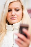 Привлекательная белокурая женщина с мобильным телефоном Стоковая Фотография RF