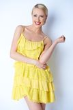 Привлекательная белокурая молодая женщина представляя в желтом платье Стоковая Фотография RF