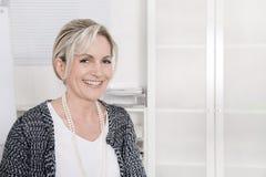 Привлекательная белокурая усмехаясь бизнес-леди на белой предпосылке стоковое изображение