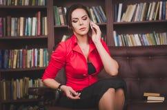Привлекательная бизнес-леди в офисе одевает сидеть на коже стоковая фотография rf