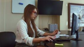 Привлекательная бизнес-леди работая с компьютером в офисе видеоматериал