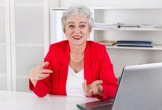 Привлекательная более старая усмехаясь старшая коммерсантка сидя на столе мы Стоковая Фотография RF