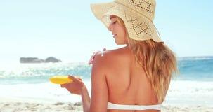 Привлекательная блондинка при шляпа кладя сливк солнца видеоматериал