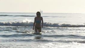 Привлекательная влажная молодая женщина приходя вне от океана в замедленном движении видеоматериал